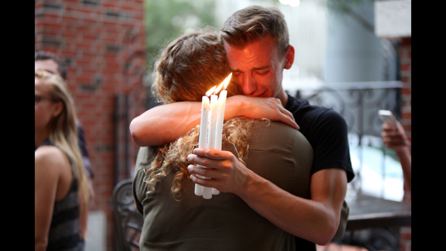 Brett Morian, from Daytona Beach, hugs an attendee during the candlelight vigil at Ember in Orlando, Fla., on Sunday, June 12, 2016. (Joshua Lim/Orlando Sentinel via AP)